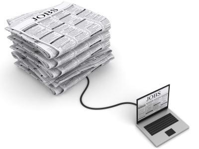 Laptop verbunden mit Zeitungsanzeigen Jobbörse
